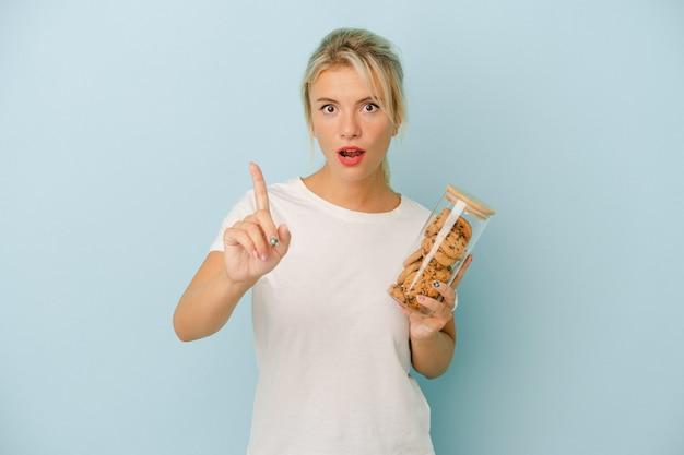 アイデア、インスピレーションの概念を持つ青い背景で隔離のクッキーを保持している若いロシアの女性。