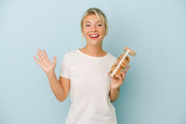 青い背景に分離されたクッキーを保持している若いロシアの女性は、嬉しい驚きを受け取り、興奮し、手を上げます。