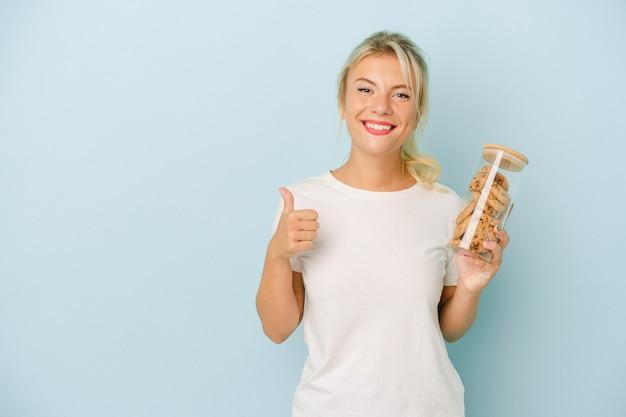 笑顔と親指を上げる青い背景で隔離のクッキーを保持している若いロシアの女性