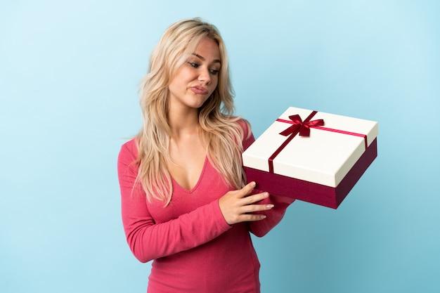 Молодая русская женщина держит подарок на синей стене с грустным выражением лица