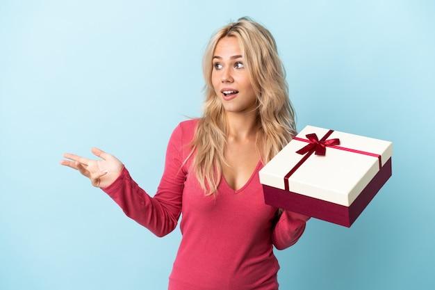 Молодая русская женщина держит подарок на синей стене с удивленным выражением лица