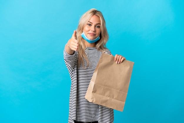 Молодая русская женщина, держащая продуктовую сумку для покупок на синем фоне, пожимая руку для заключения хорошей сделки
