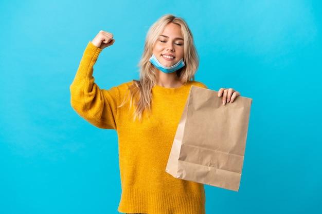 강한 제스처를 하 고 파란색에 고립 된 식료품 쇼핑 가방을 들고 젊은 러시아 여자