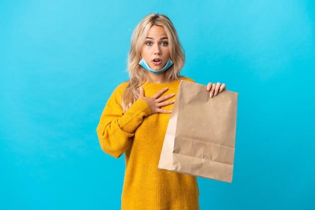 青で隔離された食料品の買い物袋を持っている若いロシアの女性は、右を見ながら驚いてショックを受けました