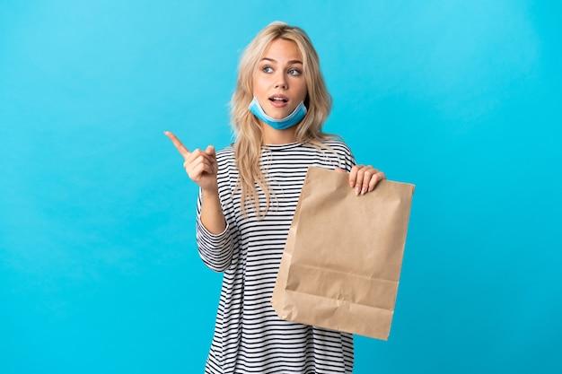 Молодая русская женщина, держащая сумку для покупок с продуктами, изолирована на синей стене, намереваясь реализовать решение, подняв палец вверх