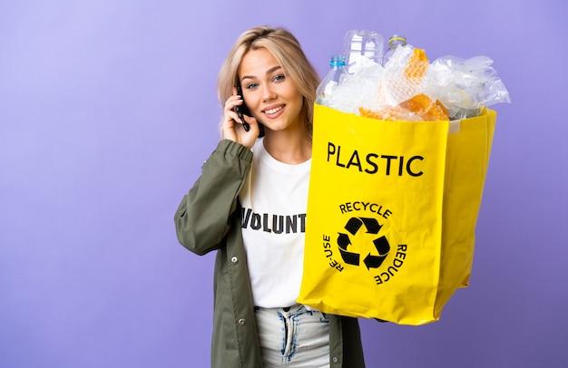 Молодая россиянка держит мешок для переработки, полный бумаги для переработки, изолирован на фиолетовом фоне, разговаривает с кем-то по мобильному телефону