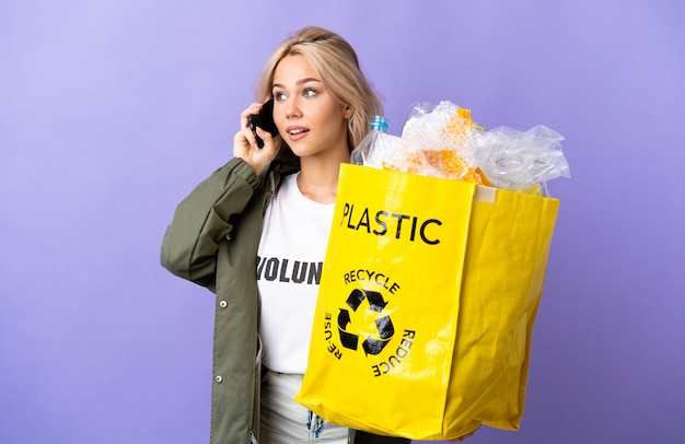 Молодая россиянка держит мешок для переработки, полный бумаги для переработки, изолирован на фиолетовом фоне, разговаривает по мобильному телефону