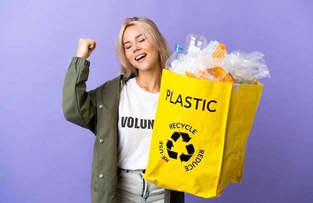 勝利を祝う紫色に分離されたリサイクルする紙でいっぱいのリサイクルバッグを保持している若いロシアの女性
