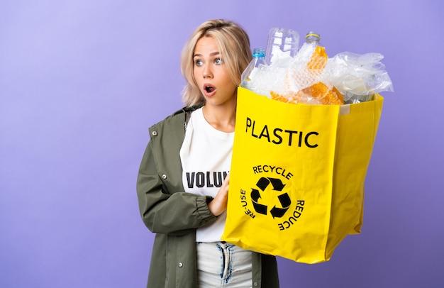 側を見ながら驚きのジェスチャーをしている紫色に分離されたリサイクルする紙でいっぱいのリサイクルバッグを保持している若いロシアの女性