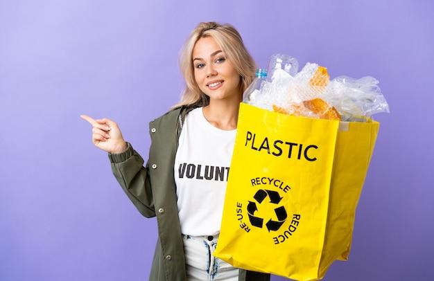 横に紫色の人差し指で隔離のリサイクルする紙でいっぱいのリサイクルバッグを保持している若いロシアの女性