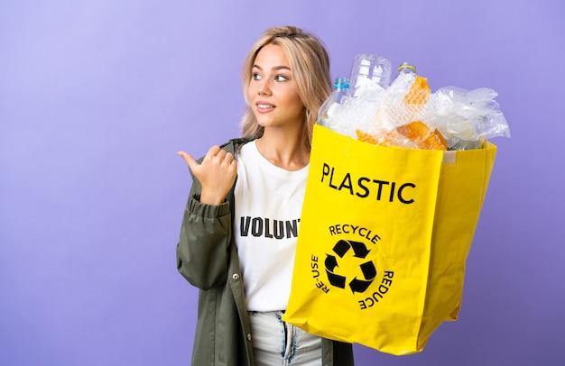 製品を提示する側を指している紫色に分離されたリサイクルする紙でいっぱいのリサイクルバッグを保持している若いロシアの女性