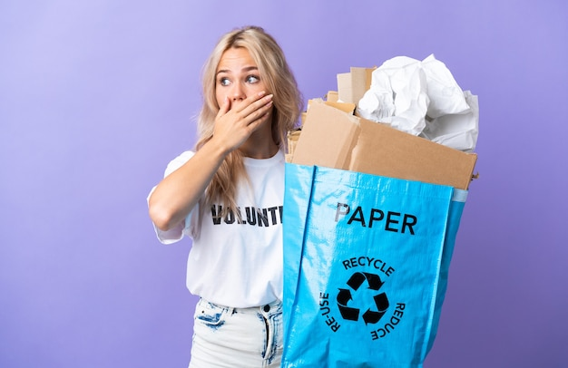 측면을 보면서 깜짝 제스처를 하 고 보라색 벽에 고립 된 재활용 종이의 전체 재활용 가방을 들고 젊은 러시아 여자