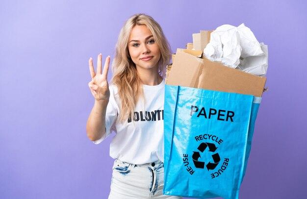 재활용 종이로 가득 찬 재활용 가방을 들고 젊은 러시아 여자는 행복하고 손가락으로 세 세 보라색 벽에 고립 재활용