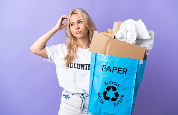 頭を掻きながら疑念を持って紫色の壁に隔離されたリサイクルする紙でいっぱいのリサイクルバッグを保持している若いロシアの女性