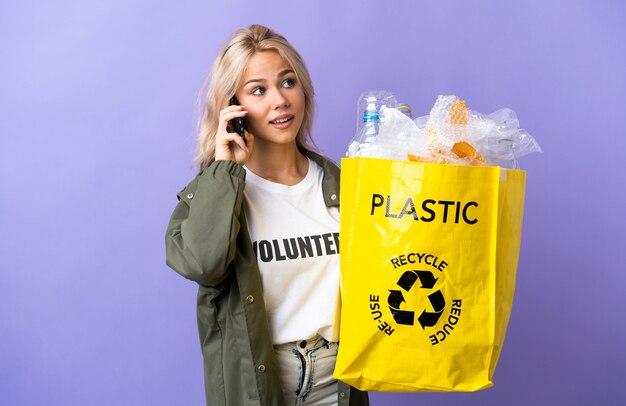 誰かと携帯電話との会話を維持している紫色の壁に隔離されたリサイクルする紙でいっぱいのリサイクルバッグを保持している若いロシアの女性