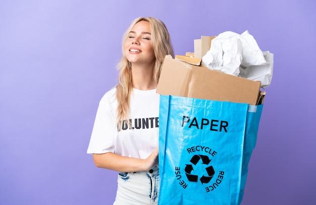 笑いながら紫色の壁に隔離されたリサイクルする紙でいっぱいのリサイクルバッグを保持している若いロシアの女性