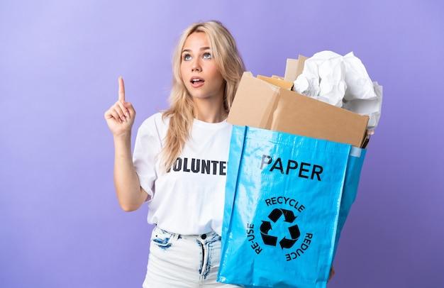 재활용 종이로 가득 찬 재활용 가방을 들고 젊은 러시아 여자는 위쪽을 가리키는 보라색 벽에 고립 된 재활용