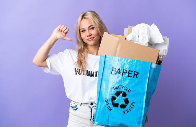 誇りと自己満足の紫色の壁に隔離されたリサイクルする紙でいっぱいのリサイクルバッグを保持している若いロシアの女性