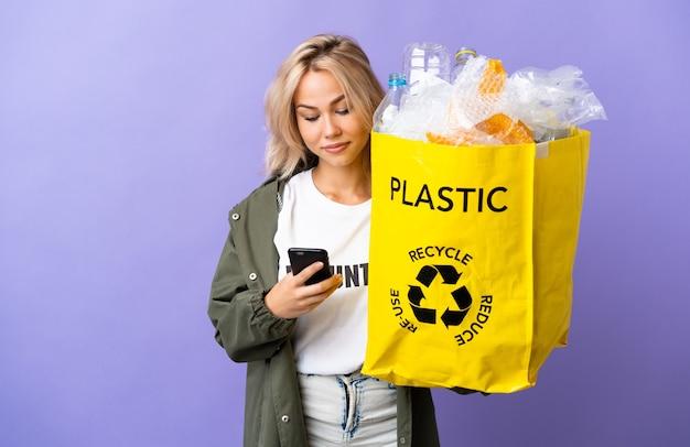 モバイルでメッセージを送信する紫色の壁に隔離されたリサイクルする紙でいっぱいのリサイクルバッグを保持している若いロシアの女性