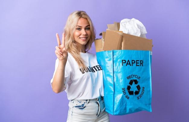 웃 고 승리 기호를 보여주는 보라색 벽에 고립 된 재활용 종이의 전체 재활용 가방을 들고 젊은 러시아 여자