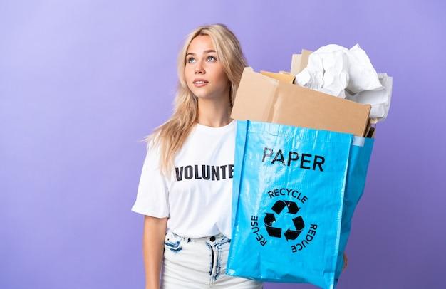 찾는 동안 아이디어를 생각하는 보라색 벽에 고립 재활용 종이의 전체 재활용 가방을 들고 젊은 러시아 여자