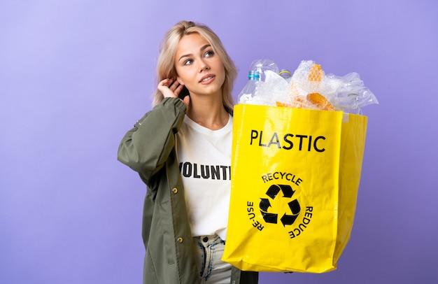 아이디어를 생각하는 보라색 벽에 고립 된 재활용 종이의 전체 재활용 가방을 들고 젊은 러시아 여자
