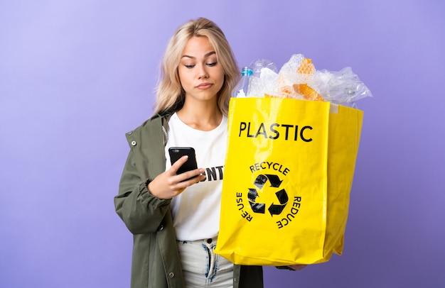 紫色の壁に孤立したリサイクルするために紙でいっぱいのリサイクルバッグを持っている若いロシアの女性が考えてメッセージを送信