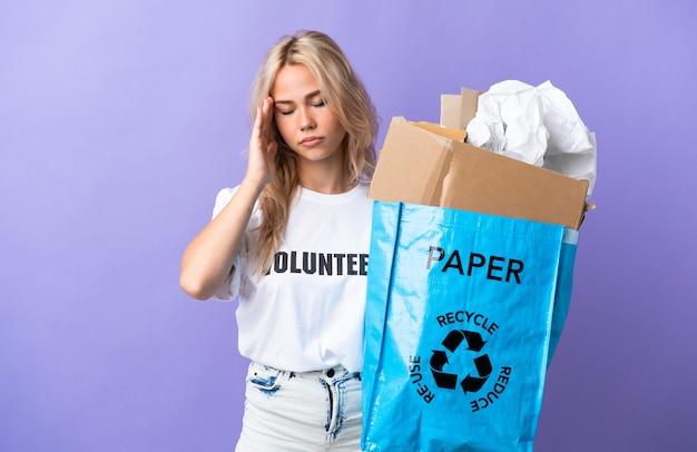 두통과 보라색 벽에 고립 된 재활용 종이의 전체 재활용 가방을 들고 젊은 러시아 여자