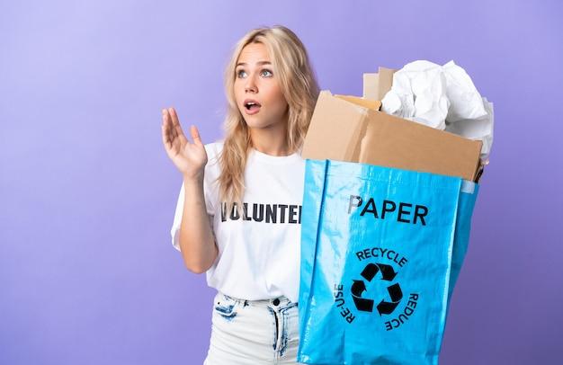 驚きの表情で紫色に分離されたリサイクルする紙でいっぱいのリサイクルバッグを保持している若いロシアの女性