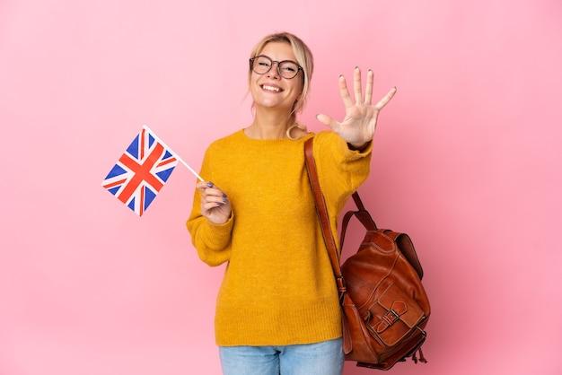 손가락으로 5 세 분홍색 배경에 고립 된 영국 국기를 들고 젊은 러시아 여자