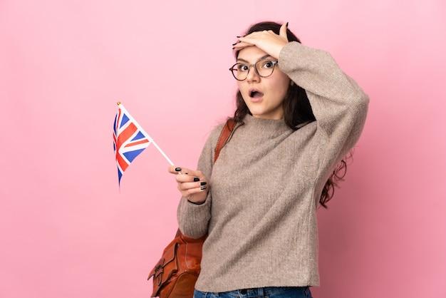 Молодая россиянка держит флаг соединенного королевства на розовом фоне, делая неожиданный жест, глядя в сторону