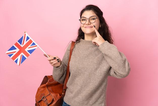 Молодая россиянка держит флаг соединенного королевства на розовом фоне, показывая жест рукой вверх