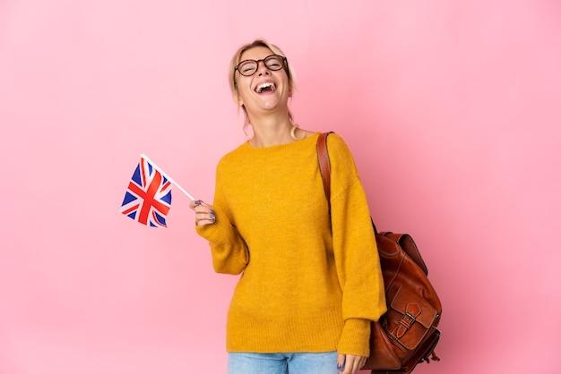 분홍색 배경 웃음에 고립 된 영국 국기를 들고 젊은 러시아 여자