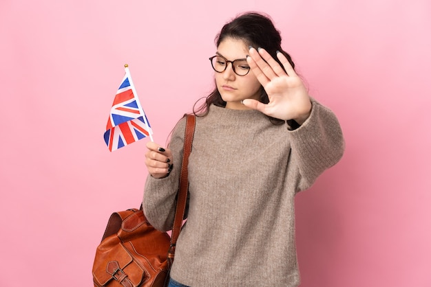 ピンクの背景に分離されたイギリスの旗を保持している若いロシアの女性