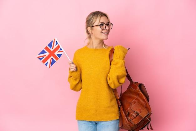 Молодая россиянка держит флаг соединенного королевства на розовом фоне, указывая в сторону, чтобы представить продукт