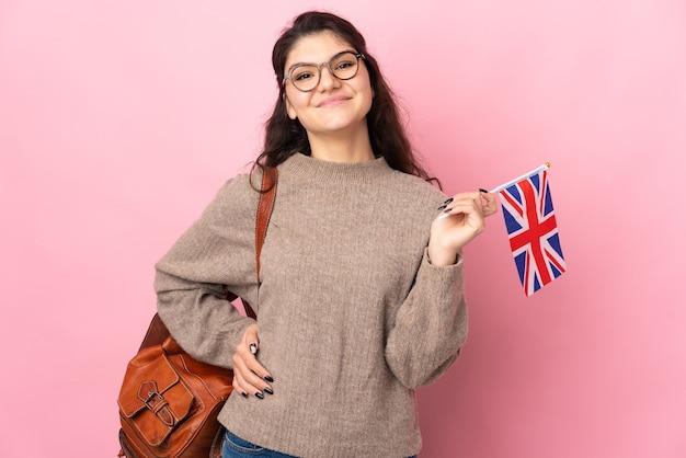 ピンクの背景に分離されたイギリスの旗を保持している若いロシアの女性は、腰に腕と笑顔でポーズをとる