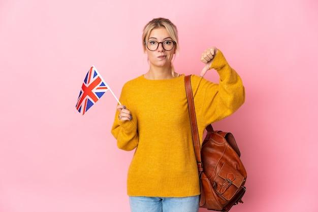 Молодая россиянка держит флаг соединенного королевства на розовом фоне, показывая большой палец вниз с негативным выражением лица