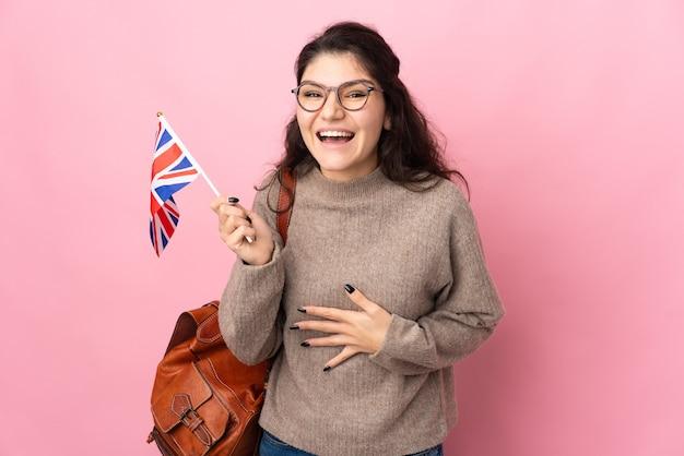たくさん笑ってピンクの背景に分離されたイギリスの旗を保持している若いロシアの女性