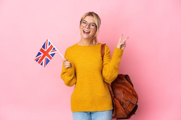Молодая русская женщина, держащая флаг соединенного королевства, изолированная на розовом фоне, улыбается и показывает знак победы