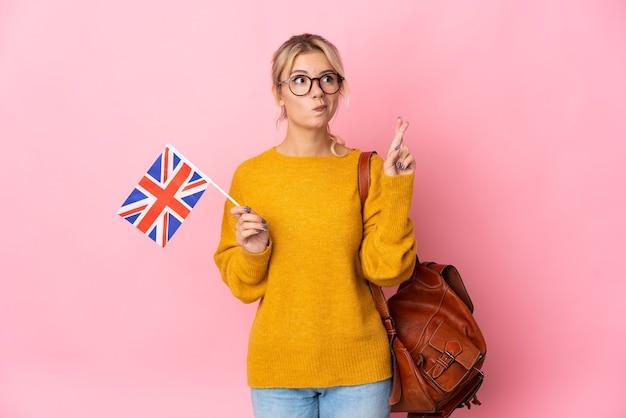 Молодая россиянка держит флаг соединенного королевства на розовом фоне со скрещенными пальцами и желает всего наилучшего