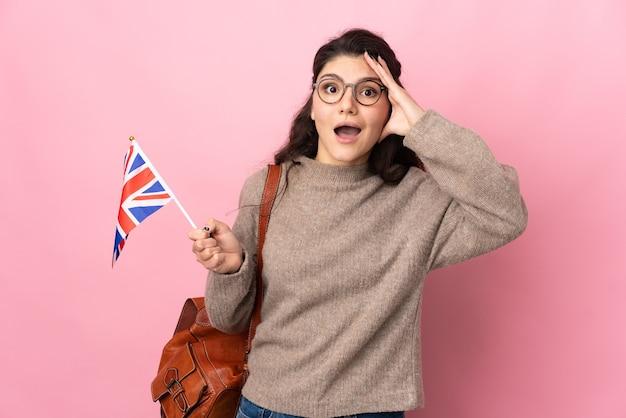 驚きの表情でピンクの背景に分離されたイギリスの旗を保持している若いロシアの女性