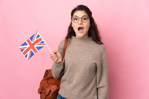 Молодая россиянка держит флаг соединенного королевства на розовом фоне с удивленным выражением лица