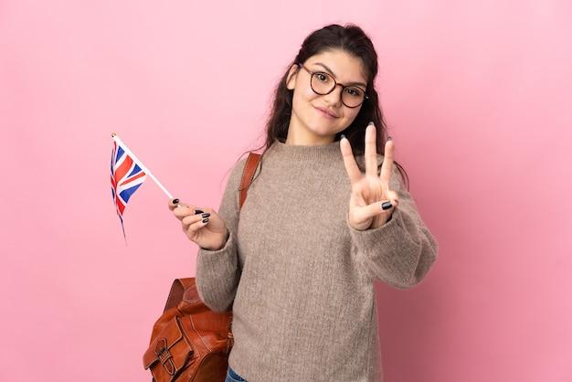 분홍색 벽 행복에 고립 된 영국 국기를 들고 손가락으로 세 세 젊은 러시아 여자