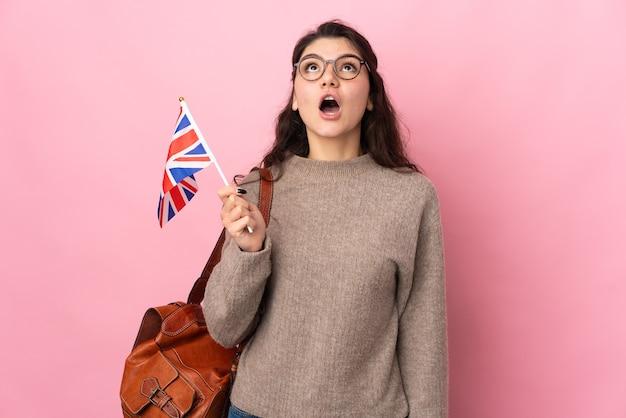 Молодая русская женщина, держащая флаг соединенного королевства, изолированная на розовой стене, смотрит вверх и с удивленным выражением лица