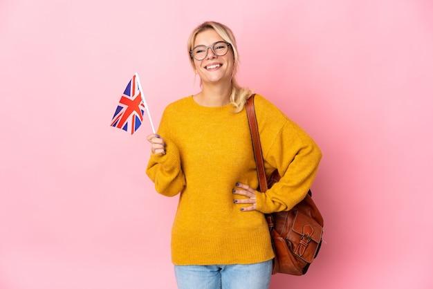 엉덩이에 팔을 포즈와 미소 핑크 벽에 고립 된 영국 국기를 들고 젊은 러시아 여자