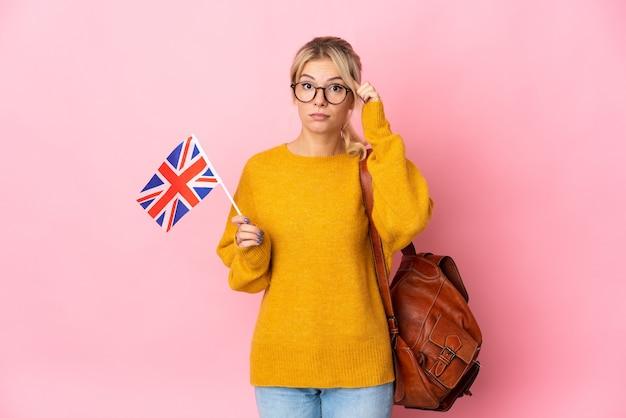 Молодая русская женщина, держащая флаг соединенного королевства, изолированная на розовой стене, думает об идее