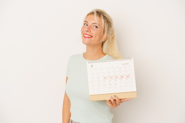Young russian woman holding a calendar isolated on white background looks aside smiling, cheerful and pleasant.