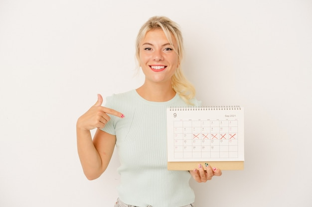 Young russian woman holding a calendar isolated on white background person pointing by hand to a shirt copy space, proud and confident