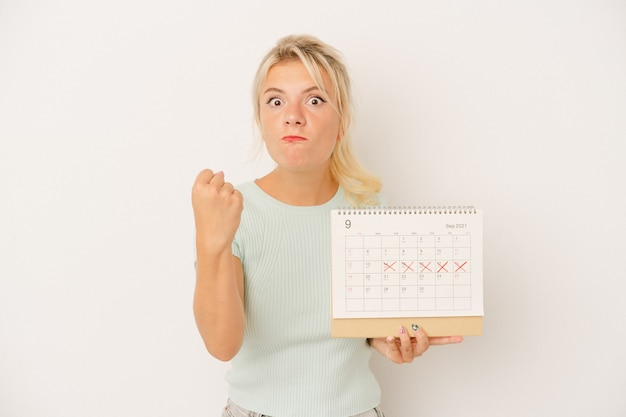 Young russian woman holding a calendar isolated on white background showing fist to camera, aggressive facial expression.