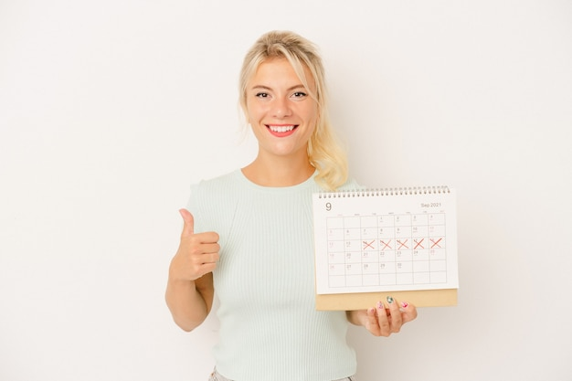 Young russian woman holding a calendar isolated on white background smiling and raising thumb up